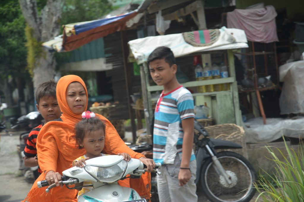 Muslim woman riding motorcycle on streets in Medan, Indonesia