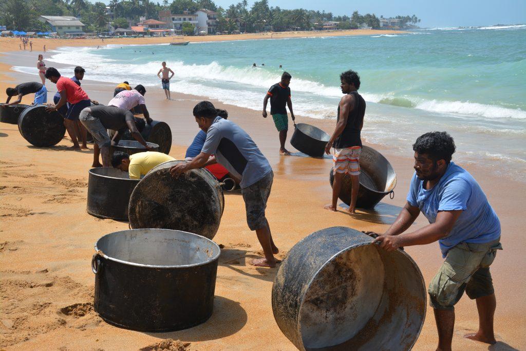 Men washing pots for July Poya Festival, Unawatuna, Sri Lanka