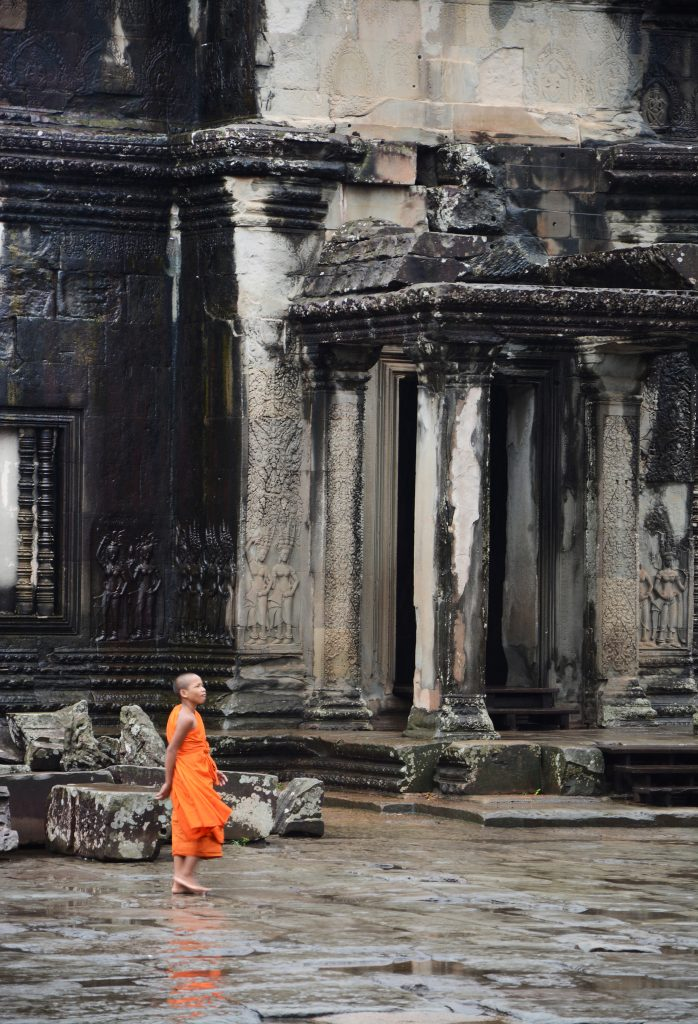 monk strolling through Angkor Wat temple, Cambodia