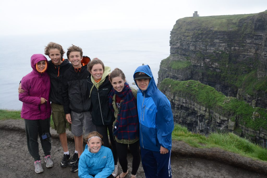 Kids in group hiking along Cliffs of Moher, Ireland