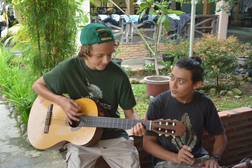 Nathan playing guitar with locals in Sumatra, Indonesia