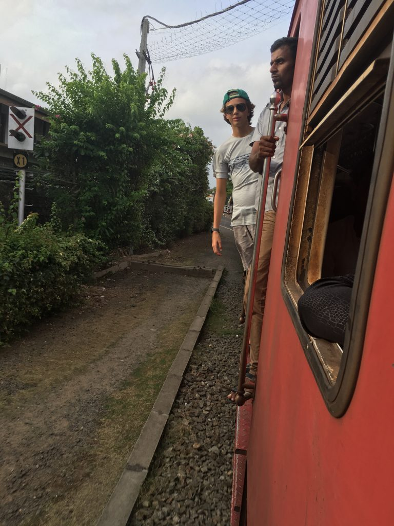 Nathan in open doorway of train from Colombo to Galle on a family trip in Sri Lanka